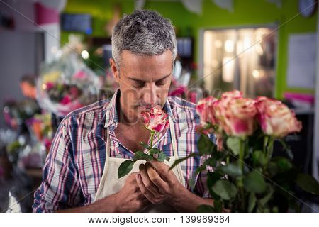 Male florist smelling flower at his flower shop
