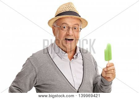 Excited elderly person holding a green popsicle and looking at the camera isolated on white background