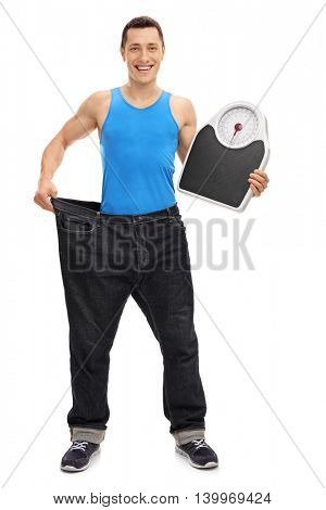 Full length portrait of a guy in large pair of jeans holding a weight scale isolated on white background