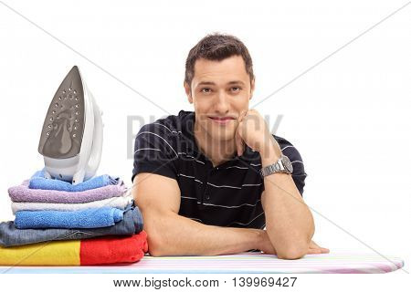 Cheerful guy posing behind an ironing board with a pile of clothes on it isolated on white background