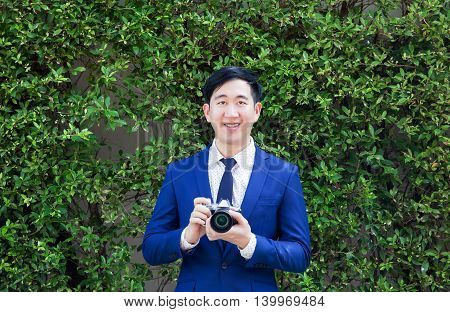 Smiling Asian Professional Photographer Holding Vintage Camera