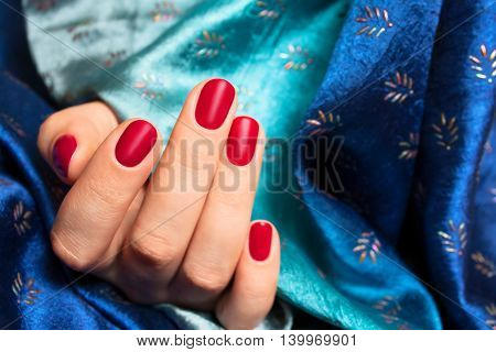 Hand of the girl with red nails over blue silk