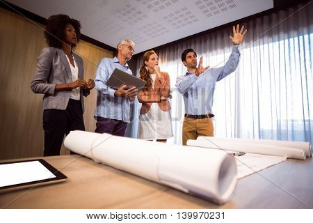 Man framing with hand while standing in board room with colleagues at office
