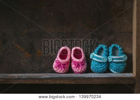 Crochet baby booties on a wooden shelf.