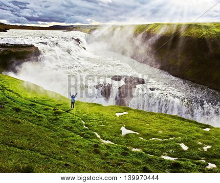 On the hillside woman thrilled looking at the boiling abyss. Powerful Gullfoss in Iceland.