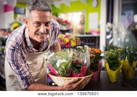 Portrait of male florist arranging bouquet of flower at his flower shop