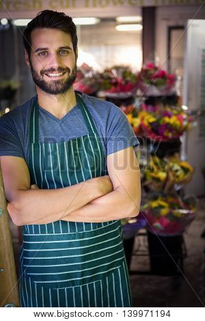 Portrait of male florist with arms crossed in flower shop