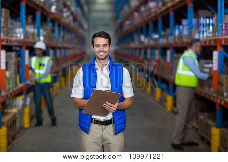 Worker looking at camera in warehouse