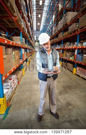 Worker looking at clipboard in warehouse