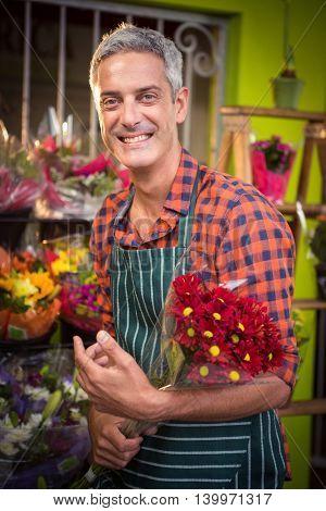 Portrait of male florist holding flower bouquet at his flower shop
