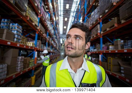 Concentrate worker in warehouse looking up