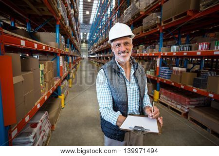 Smiling worker looking at camera in warehouse