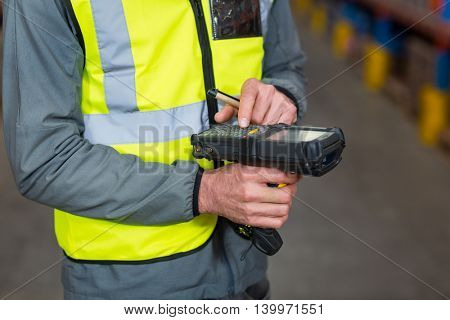 Close-up of worker using digital equipment in warehouse