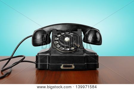 Vintage Phones - Black a retro telephone on a wooden table and a blue background.