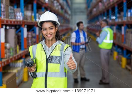 Smiling female worker with thumb up in warehouse