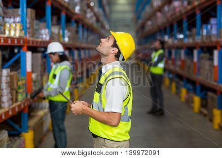 Worker with yellow safety vest looking up in warehouse