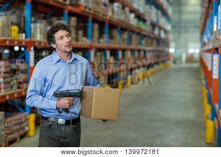 Standing worker holding a box in warehouse