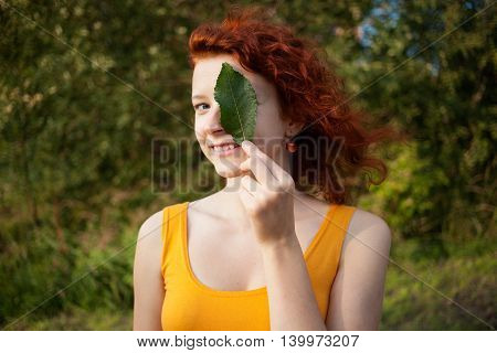 Close up portrait of a ginger girl carrying a green leaf at the eye