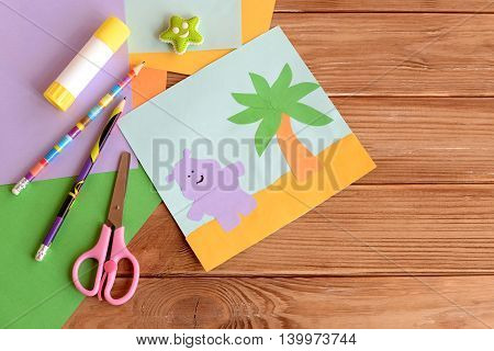 Paper hippo and palm tree applique, colored paper sheets, scissors, pencils, glue, eraser on wooden background with blank space for text. Funny children background. Art and craft project for kids
