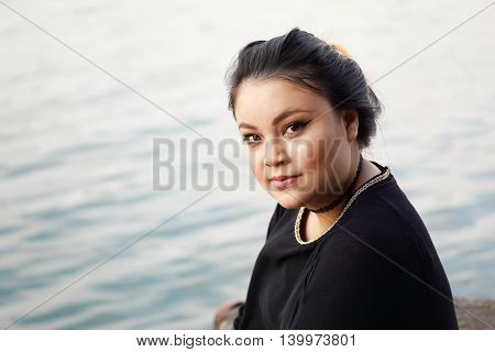 young asian woman sitting by the water. with copy space.