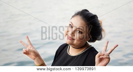 happy young asian woman making double V sign with both hands