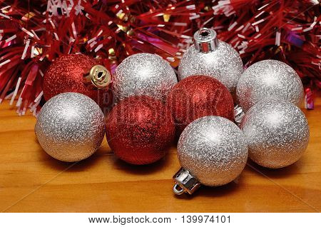 Red and silver Christmas tree baubles on a wooden background