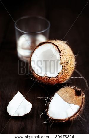 Fresh Coconut over dark wooden background. Close up of coco nut on a wooden table with copy space