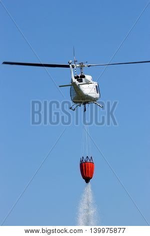 Helicopter with a Bambi bucket filled with water to fight a forest fire