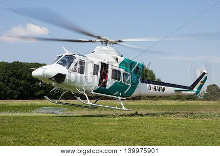 AHLEN GERMANY - JUN 5 2016: Close up view of a Bell 412SP helicopter kicking up grass while landing