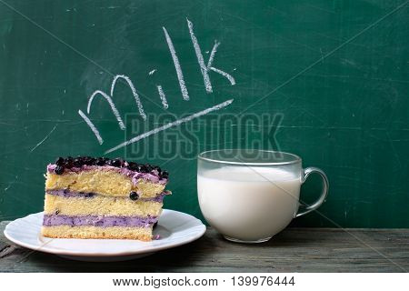glass cup of fresh natural healthy milk and text word on green school blackboard with blueberry cake on plate copy space