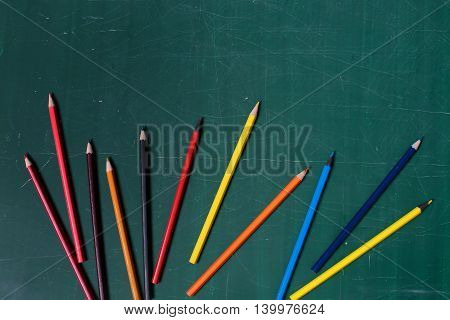 many colorful stationary of pencils for drawing or painting art different colors laying on green school blackboard or desk with nobody copy space