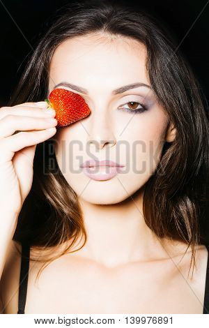 young woman with pretty face and sexy female mouth with lips holding red sweet strawberry berry fruit in hand on black background closeup