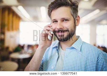 Portrait of smiling businessman using mobile phone in office cafeteria