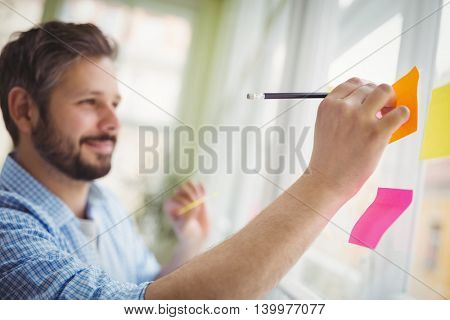 Happy businessman writing on adhesive notes at creative office