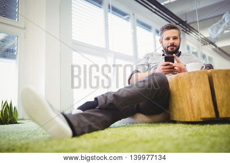 Portrait of businessman using mobile phone at creative office
