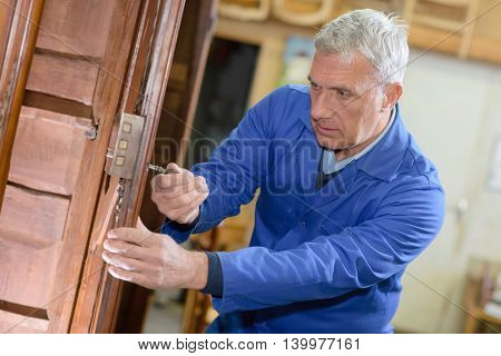 senior male repairing a wooden door latch
