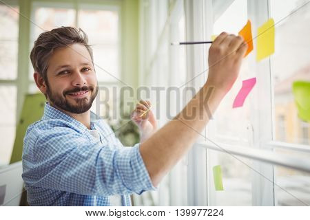 Portrait of businessman writing on adhesive notes at creative office