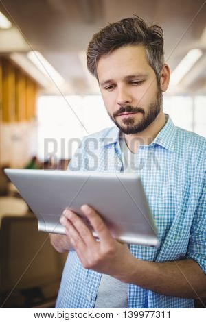 Young businessman holding digital tablet in office