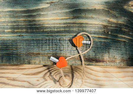 Two red heart clothespins on rope on grey wooden board on timber background