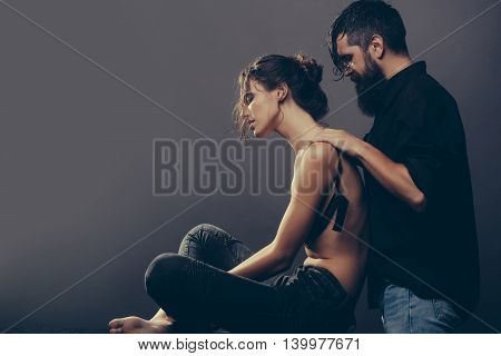 young couple of pretty sexy woman in black jeans and bra has slim body and handsome bearded man with long beard in shirt doing massage on grey background copy space