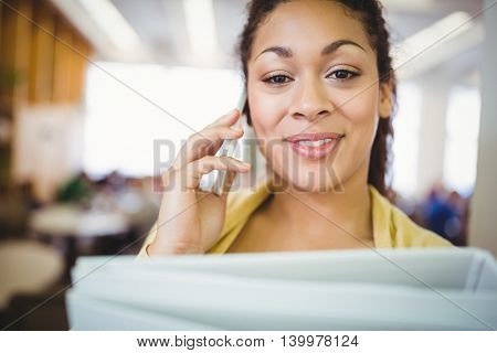 Portait of businesswoman holding files while using mobile phone in office cafeteria