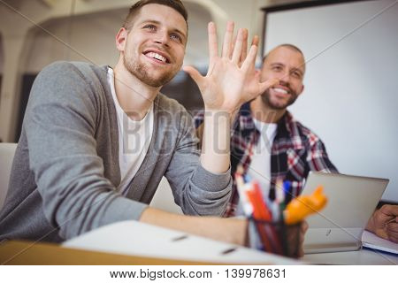 Happy young businessmen gesturing at desk in creative office