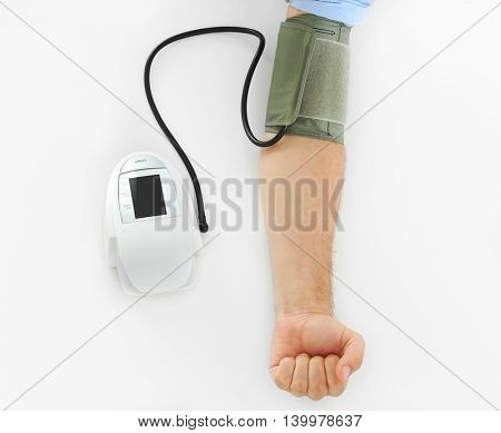 Male hand with tonometer on white background