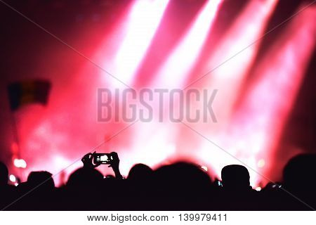 Mobile phone recording a live concert. Stage lights in the background