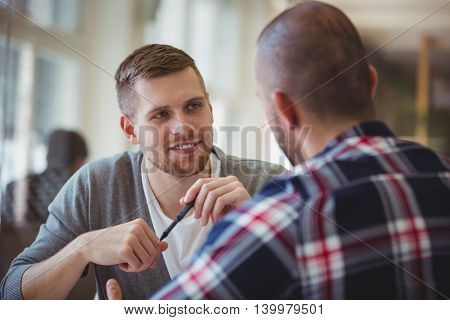 Young businessman discussing with colleague in creative office