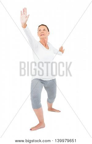 Mature woman with arms outstretched while exercising on white background