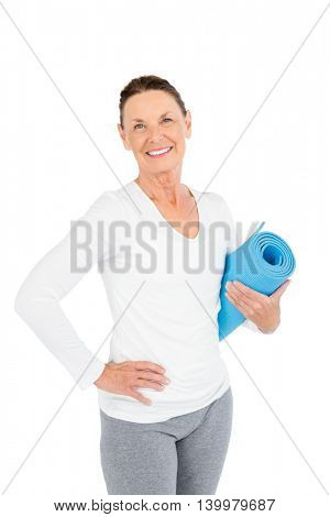 Portrait of smiling mature woman holding exercise mat while standing on white background