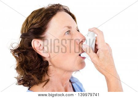 Close-up of mature woman using asthma inhaler against white background