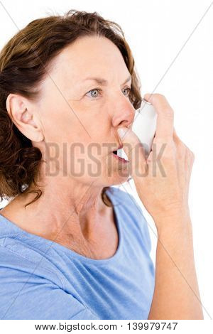 Mature woman using asthma inhaler against white background