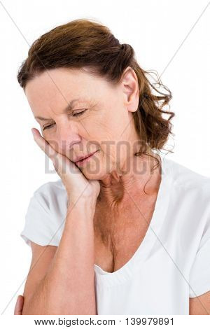 Mature woman having toothache against white background